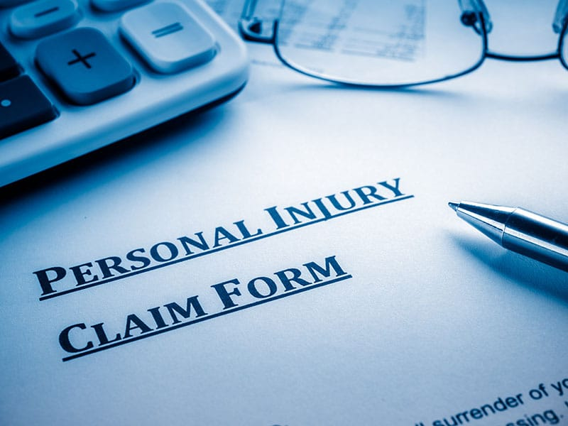 A Personal Injury Claim Form sits on a desk